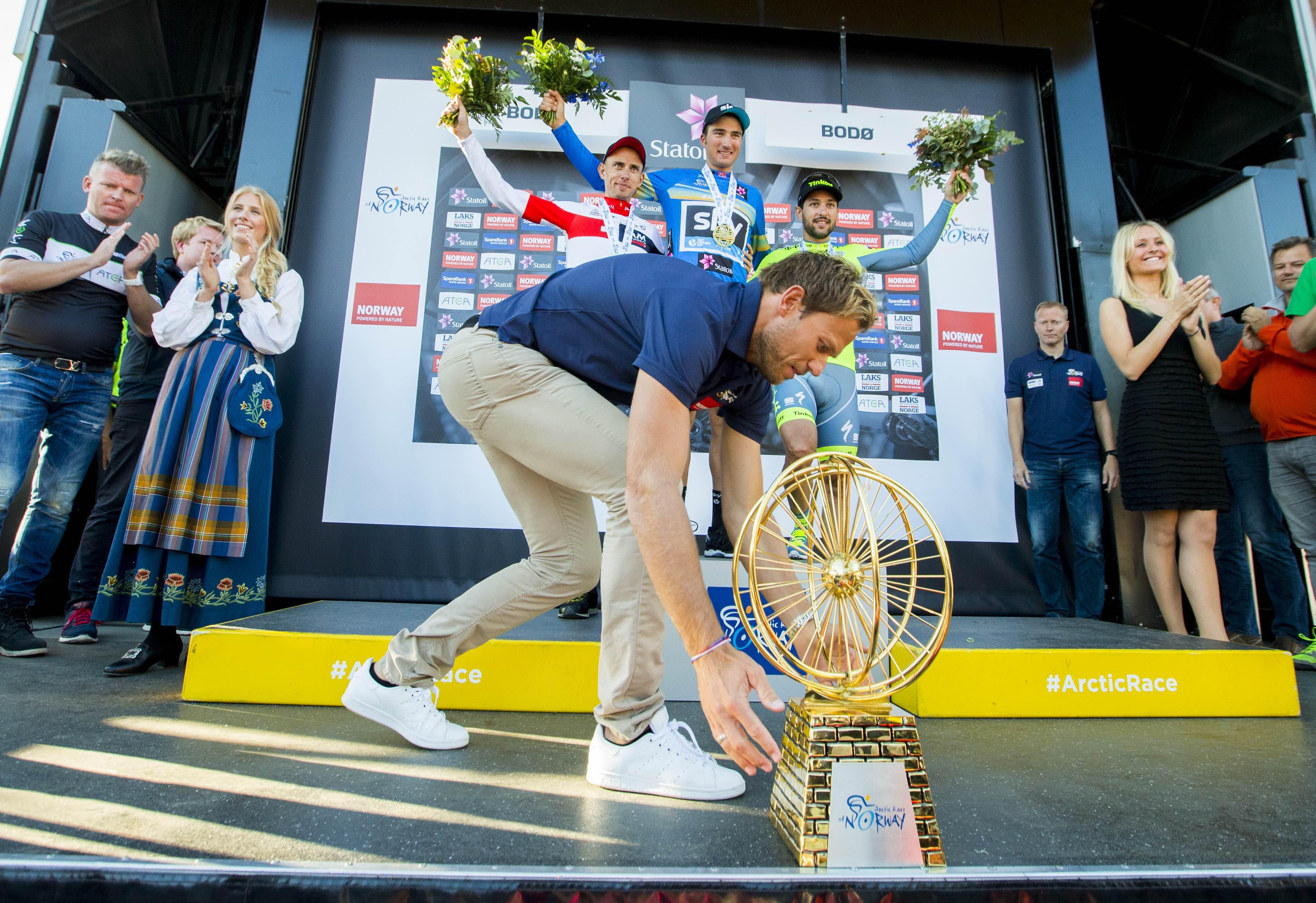 Thor Hushovd, ambassad¯r og tidligere vinner av Arctic Race of Norway, plukker opp sammenlagttrofeet for gi det til Gianni Moscon fra Italia (Team Sky) etter fjerde og siste etappe i sykkelrittet Arctic Race of Norway s¯ndag.